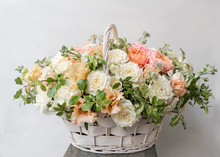 Wicker Basket With Mix Beautiful Flowers On Wooden Table Near Gray Wall. Beautiful Garden Flowers In The Arrangement , The Work Of A Professional Florist. European Floral Shop