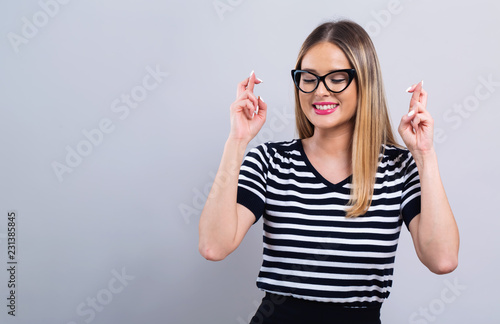 Stampa su Tela Young woman crossing her fingers and wishing for good luck on a gray background
