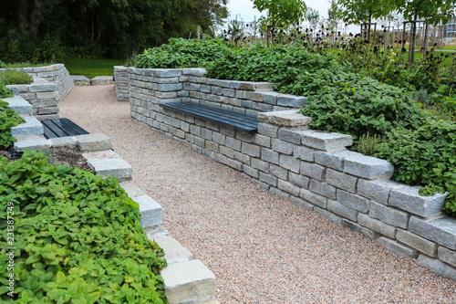 Moderner Garten- und Landschaftsbau: Gehweg und Mauern aus Natursteinen mit integrierten Sitzbänken und Anpflanzungen