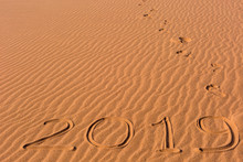 2019 Inscription Written On Golden Wavy Beach Sand Dunes With Footprints