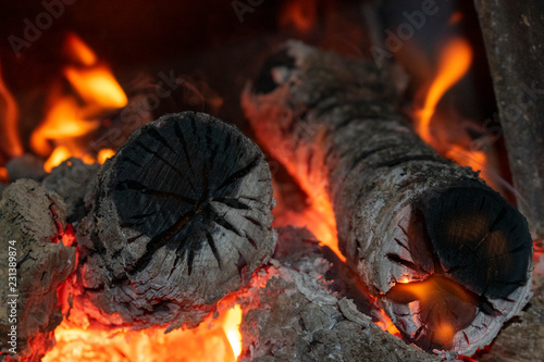 Fotografiet  burning logs and charcoal in the furnace, closeup
