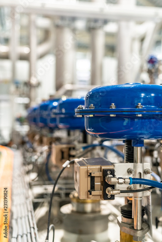 Photo pneumatic valves in a row in a large industrial plant