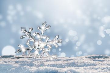 Leuchtender großer Eiskristall im Schnee, Bokeh des Winters leuchtet im Hintergrund