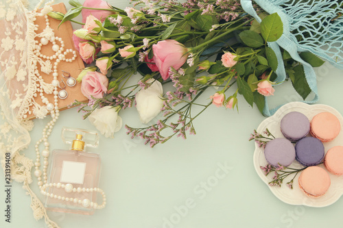 fresh vintage perfume bottle next to aromatic flowers on wooden table.