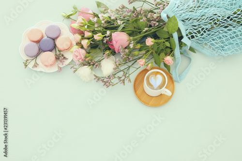 plate of macaroons over wooden table cofee and flowers.
