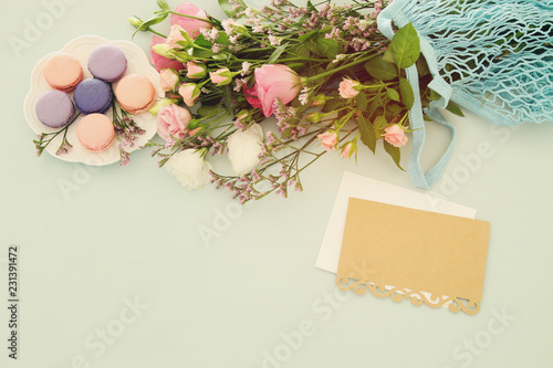 plate of macaroons over wooden table, emprty note and flowers.