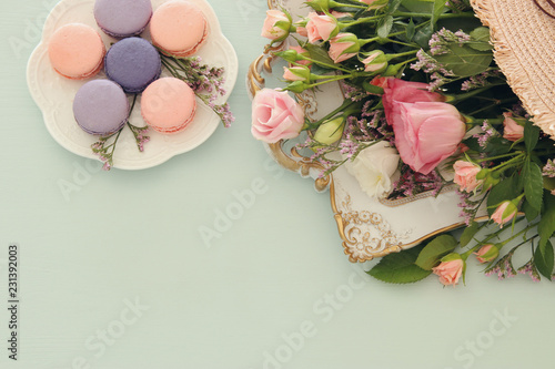 plate of macaroons over wooden table and flowers.