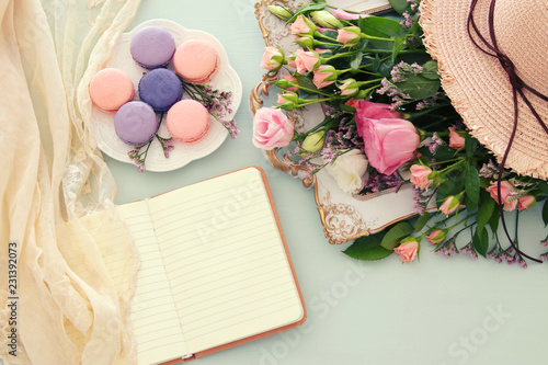 plate of macaroons over wooden table, emprty notebook and flowers.