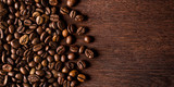 Fototapeta Kitchen - fresh roasted coffee beans on natural dark oak wood panorama wide wooden closeup macro background