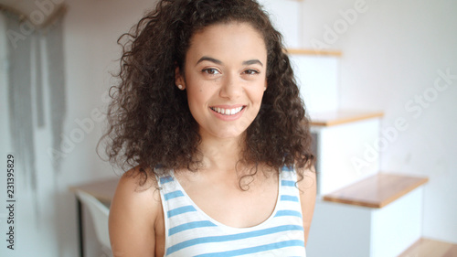Portrait of a beautiful young woman smiling at the camera in a kitchen Tableau sur Toile