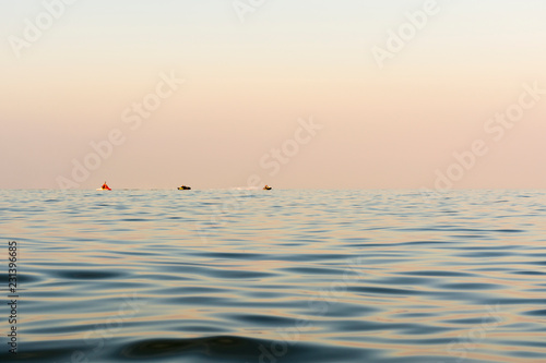 Fotografía  evening sea with waves, far away on a horizon line floating water bike, nature a
