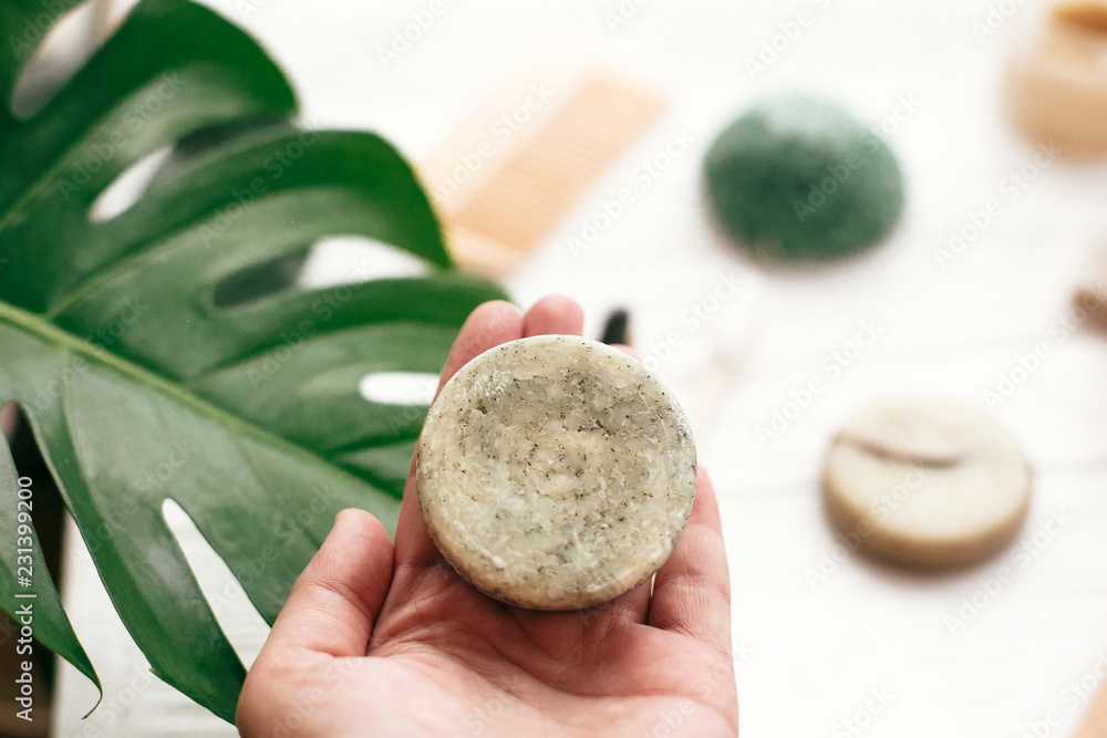 Fototapeta Zero waste. Choice plastic free eco products. Hand holding natural solid shampoo bar on background of bamboo brush, deodorant, sponge on white wood with green monstera leaves.