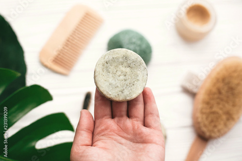 Fotografie, Obraz  Hand holding natural solid shampoo bar on background of bamboo brush, deodorant, sponge on white wood with green monstera leaves