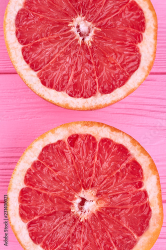 Sliced halves of fresh grapefruit. Ripe delicious grapefruit cutted on two pieces on pink wood close up.