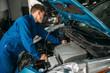Mechanic repairs car engine, motor diagnostic