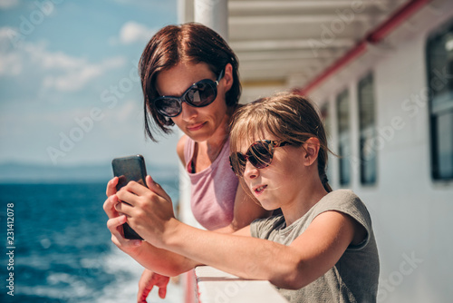 Fotografia Mother and daughter traveling on ferry and taking pictures