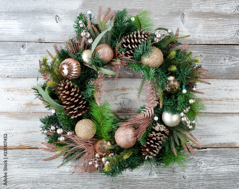 Fototapeta Christmas holiday wreath with illuminated lights on rustic white wood