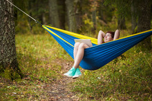Image Of Young Brunette With Hands Behind Head Resting In Hammock With Laptop In Forest