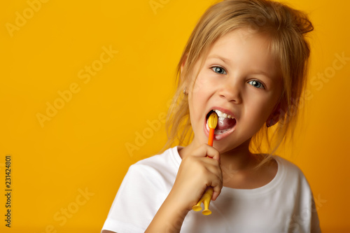 Foto  Charming little girl in white t-shirt cleaning teeth with colorful kids toothbru