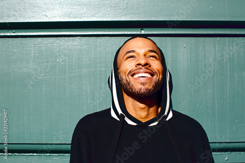 Portrait of a smiling young man with a hoodie, leaning on a green wall