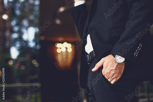 Attractive young man in dark suit and with a watch on his wrist putting his hand into the pocket of his trousers
