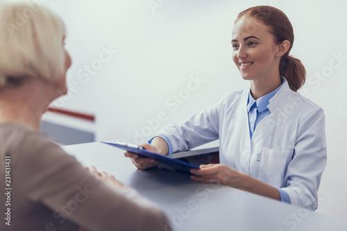 Obraz na płótnie Focus on smiling female practitioner standing at reception desk