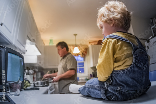 Tela Toddler boy sitting on kitchen counter watching tv while father prepares dinner