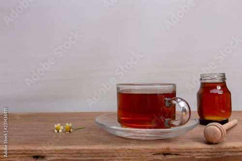 Foto op Plexiglas Thee Hot tea cup and honey on the wooden table with tea plantations background. Healthy drink with copy space