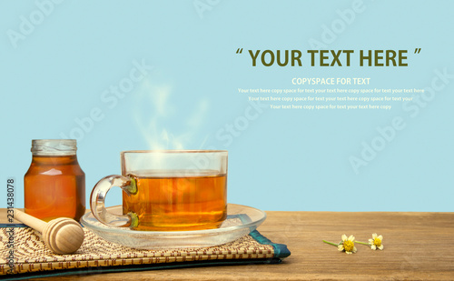 Tuinposter Thee Hot tea cup and honey on the wooden table with tea plantations background. Healthy drink with copy space