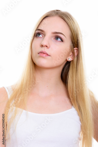 Face of young beautiful teenage girl thinking while looking up