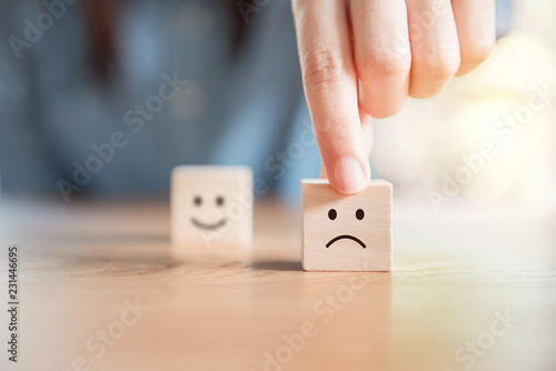 Photographie  Close up customer hand choose sad face and blurred smiley face icon on wood cube, Service rating, satisfaction concept