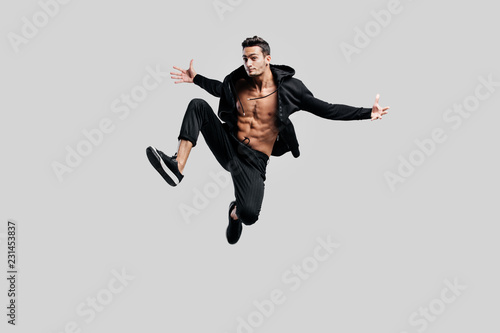 Canvas Handsome dancer of street dancing dressed in black pants and a sweatshirt on a n
