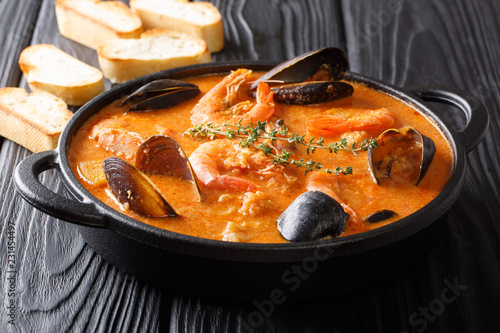 Seafood spicy soup with potatoes, shrimps, mussels, herbs and fish from a picad closeup served with toast. horizontal