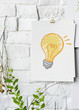 Light bulb drawn on paper poster on white wall