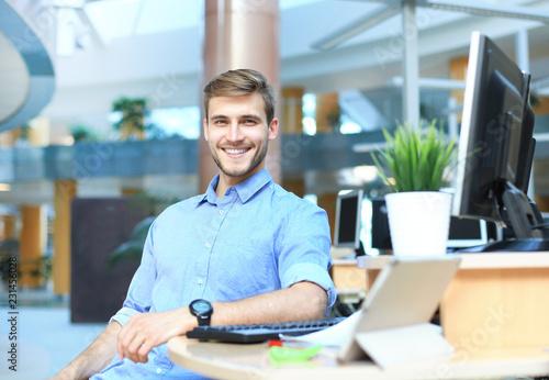 Spoed Foto op Canvas Wanddecoratie met eigen foto Portrait of happy man sitting at office desk, looking at camera, smiling.