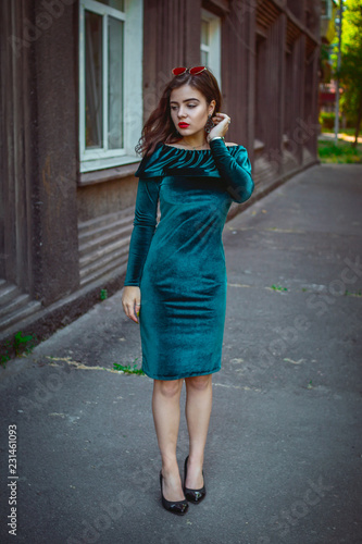Portrait of beautiful young brunette woman with bright makeup, wearing emerald green velvet dress standing