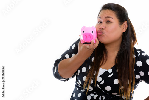Fotografija  Studio shot of young fat Asian woman puckering lips and holding