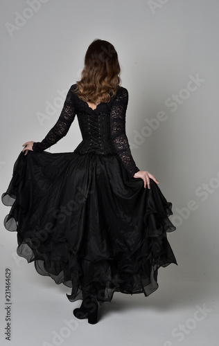 full length portrait of brunette girl wearing long black lace gown with corset Canvas