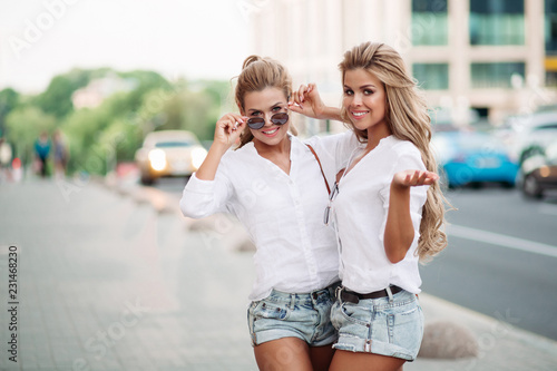 Photo Beautiful women twins embracing on street, showing peace by hands and smiling at camera
