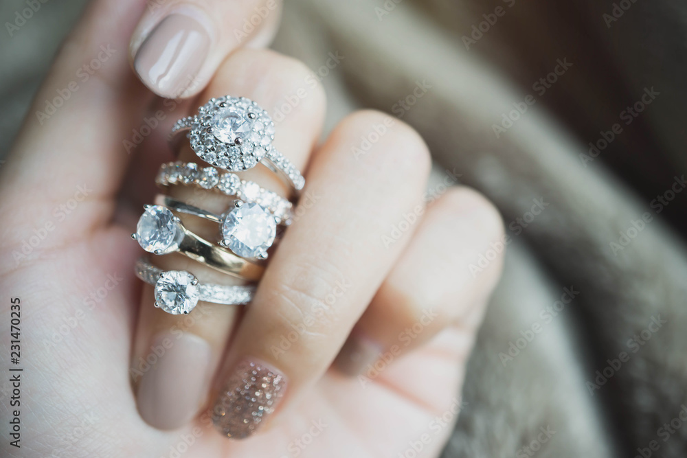 Fototapeta Close up of an elegant diamond rings on woman finger.love and wedding concept.soft and selective focus.