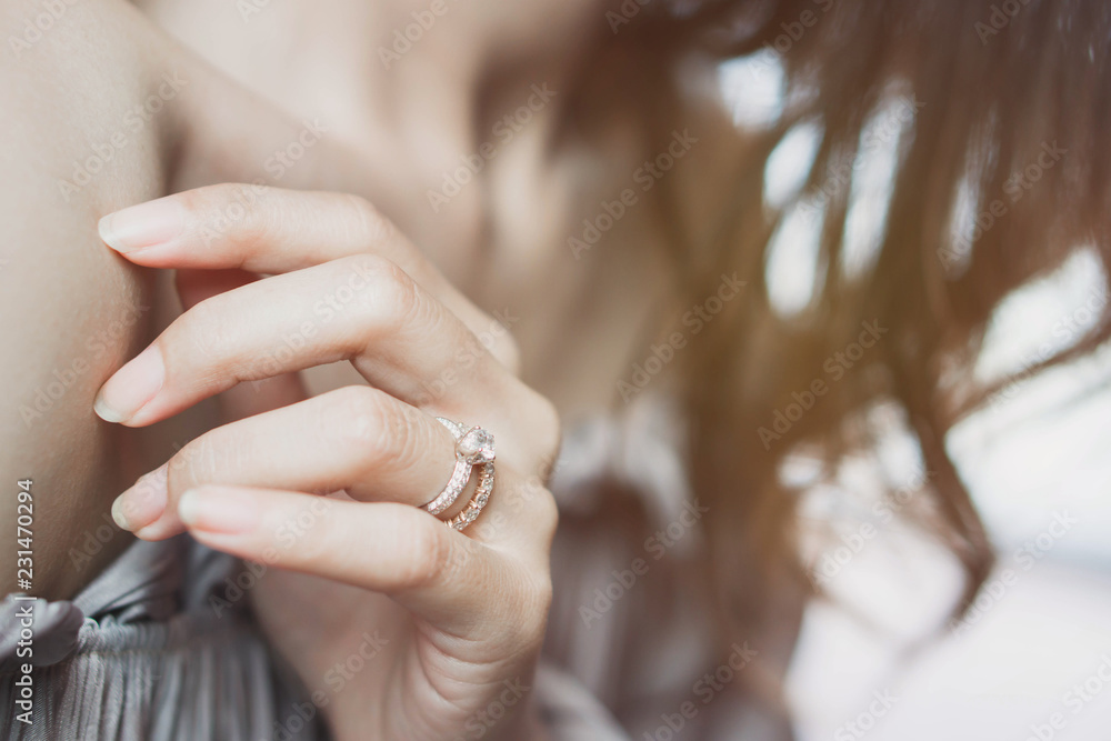 Fototapeta Blurry of an elegant diamond ring on woman finger. soft and selective focus. Love and wedding concept.