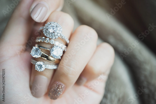 Fototapeta Close up of an elegant diamond rings on woman finger