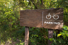 Wooden Sign Of A Bicycle Parking  Green On Forest Background. Copy Space For Adjust Your Text Or Message.
