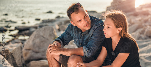 Slika na platnu Father and daughter sitting on a rocky beach and talking