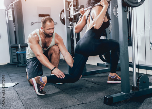 Fitness woman exercising with fitness trainer in gym Fototapet