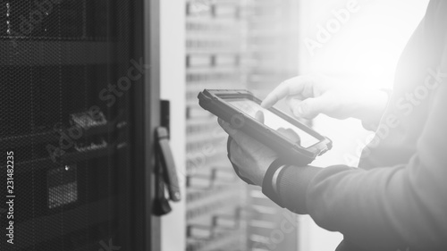 Specialist with a tablet in server room, checking the status of critical systems, monochrome effect, banner