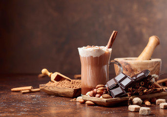 Fototapeta Cocoa with cream, cinnamon, chocolate pieces and various spices.