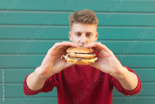 Fotografie, Obraz  Young man stands on a turquoise background and holds an appetizing burger in his hands