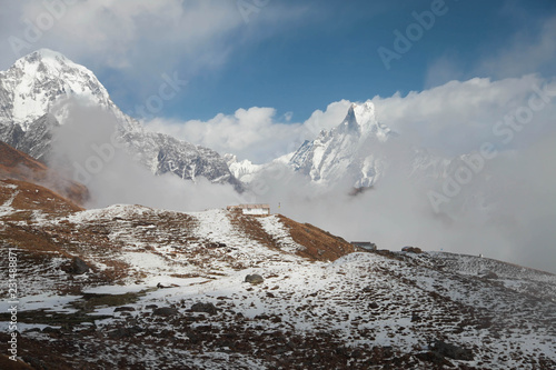Spoed Foto op Canvas Bergen Machapuchare mountain in big white clouds. Nepal.