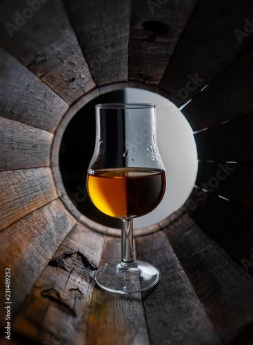 Glass of whiskey stands inside an oak barrel